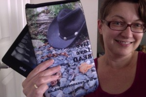 Roxanne holding up a neoprene e-reader sleeve, with cowboy hat photo plus Live, Love, READ and www.roxannesnopek.ca